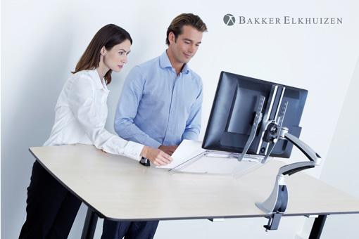Ein Mann und eine Frau arbeiten zusammen an einem Stehtisch und besprechen sich