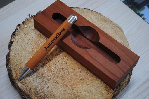 Formschöner Holzkugelschreiber mit Aufbewahrungs Holzstück auf einem kleinen Baumstamm trappiert